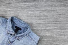 人塑造,在棕色木背景的蓝色牛仔裤衬衣 库存图片