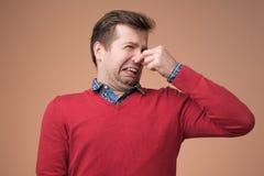 人塞住鼻子作为气味某事恶臭 库存图片