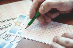 人填好一个乐透纸牌抽奖券 免版税图库摄影
