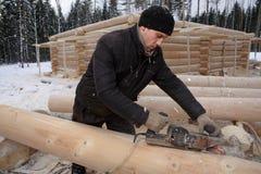 年轻人处理修建的一个木屋一本日志从plani 免版税库存图片
