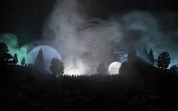 人大人群的剪影在森林里在晚上观看在上升的大满月的  与夜空机智的装饰的背景 免版税图库摄影