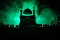人大人群的剪影在森林里在站立反对与被定调子的光束的一个被弄脏的清真寺大厦的晚上在fogg 库存图片
