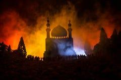 人大人群的剪影在森林里在站立反对与被定调子的光束的一个被弄脏的清真寺大厦的晚上在fogg 免版税库存图片