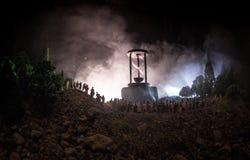 人大人群的剪影在森林里在站立反对有被定调子的光束的大滴漏的晚上在有雾的backgrou 免版税库存照片