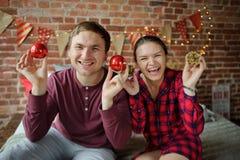 年轻人夫妇演奏圣诞树装饰 图库摄影