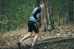 年轻人奔跑通过森林和微笑 免版税库存照片