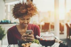 黑人女孩是射击她的在智能手机的照片食物 免版税库存图片