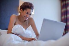 年轻黑人妇女位子在床上 免版税库存照片