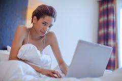 年轻黑人妇女位子在床上 免版税库存图片