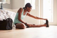 年轻黑人妇女在家坐舒展的地板 库存图片