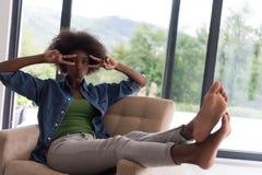 黑人妇女在家椅子的 图库摄影