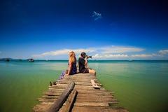人妇女坐码头照片天蓝色的海在热带 免版税库存图片
