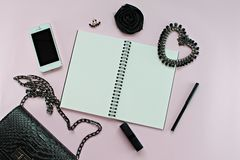 黑人妇女袋子顶视图与空白的笔记本、笔、化妆用品、辅助部件和Iphone5的在桃红色背景 免版税库存照片