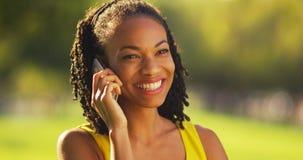 黑人妇女谈话在智能手机在公园 图库摄影