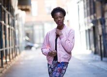 年轻黑人妇女画象在城市街道上的 图库摄影
