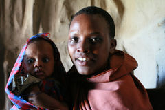 黑人妇女画象有婴孩的在小屋部落Maasai里面 免版税库存照片