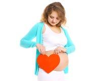 年轻人孕妇和大红色心脏在手上 免版税库存图片