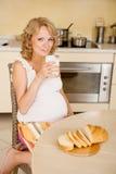 年轻人孕妇喝酸奶 免版税图库摄影