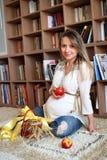 年轻人孕妇坐地板 库存图片