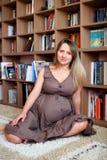 年轻人孕妇坐地板 免版税库存照片