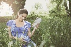 年轻人孕妇坐草和阅读书 免版税库存照片