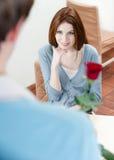 人存在一朵绯红色玫瑰给他的女朋友 免版税库存照片