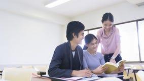 人学生读了书并且在演讲椅子教室谈话 库存照片