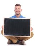年轻人安装的人拿着一个空白的黑板 库存图片