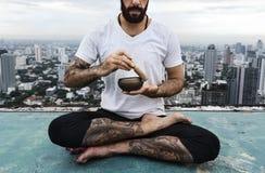 人实践瑜伽屋顶概念 免版税库存图片