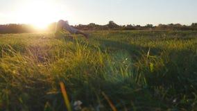 年轻人实践的瑜伽移动和位置在绿草在草甸 站立在瑜伽姿势的运动的人本质上 影视素材