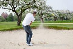 人实践的高尔夫球近的开花的果树园 免版税库存照片