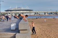 年轻人实践的parkour在城市公园 图库摄影