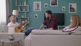 人宽射击在一个舒适客厅弹他的朋友的吉他 股票录像
