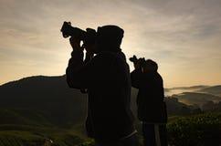 人射击剪影与dslr照相机和美丽的天空的 库存图片