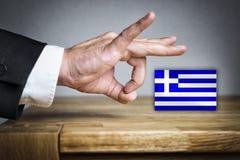人射击希腊旗子  免版税库存照片