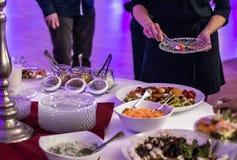 人小组在食物桌豪华餐馆的承办酒席自助餐用肉、面包和另外沙拉 免版税库存图片