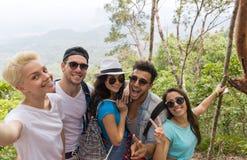 人小组拍在美好的山风景的Selfie照片,迁徙在森林、混合种族年轻愉快人和的妇女里 库存照片