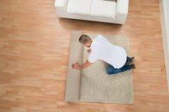 年轻人展开的地毯 免版税库存照片