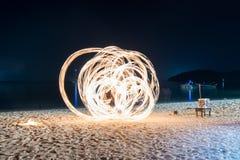 人展示在海滩的旋转火 免版税库存图片