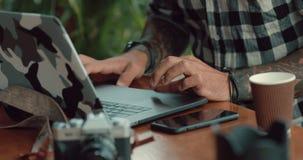 人工作在咖啡馆特写镜头的手提电脑旁边的手自由职业者 影视素材