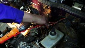 人工作者的手修理黄色和红色缆绳里面发动机 影视素材