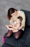 人工喂养她的婴孩的母亲的嫩图象 免版税图库摄影