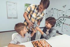人带来了两个乏味男孩一个灰色机器人 在他们旁边立场有棋子的一杆棋枰 库存图片