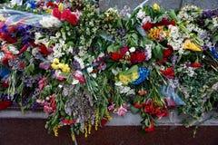 人带来的花给灼烧的`永恒火`在法西斯主义, 5月9日的胜利天 免版税库存图片