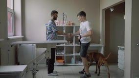 人带领在皮带的一条狗一个兽医诊所 影视素材