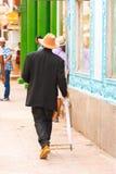 人帽子的和有伞的步行沿着向下街道,哈瓦那,古巴 垂直 复制文本的空间 免版税库存图片