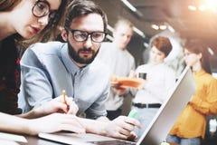 人年轻队一起研究一个新的项目在一个现代顶楼办公室 创造一新理念 工作在膝上型计算机和paperwor 库存图片