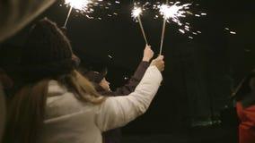 人庆祝在街道上的新年有闪烁发光物的 r 愉快地和快乐,人们庆祝新年  股票视频