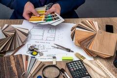 人建筑师画与色板显示的一个房子计划家具的 库存图片