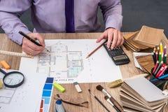 人建筑师画与色板显示的一个房子计划家具的 免版税库存照片